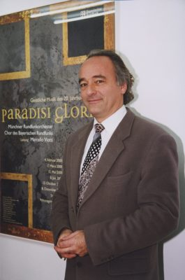 Marcello Viotti vor einem Plakat der Reihe Paradisi gloria (BR/Foto Sessner)